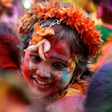A young girl with her face smeared with colored powder, smiles during celebration of Holi festival in Calcutta, India. [Bikas Das/AP]